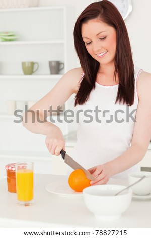 Young attractive red-haired woman cutting an orange in the kitchen in her apartment