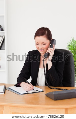 Young attractive red-haired woman in suit writing on a notepad and phoning while sitting in an office