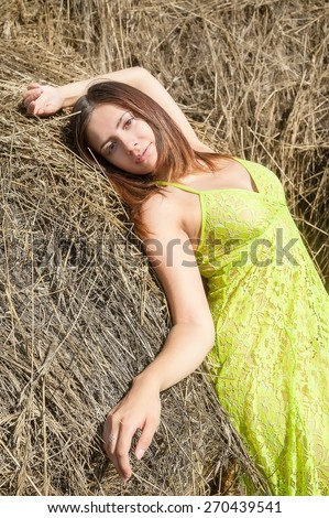 Young attractive red-haired woman relaxing on hay stack - stock photo