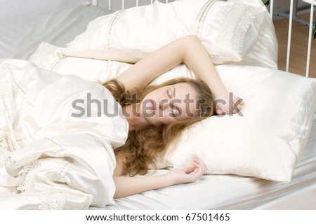 young attractive redhead caucasian female sleeping in bed at home - stock photo