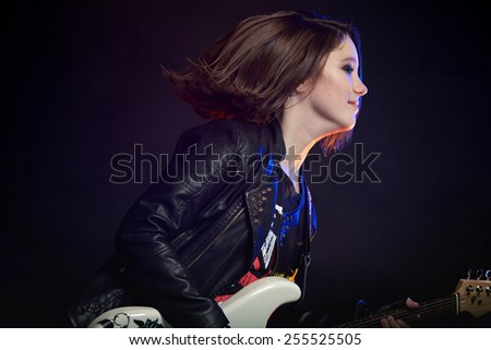 Young attractive rock girl playing the electric guitar against a dark background - stock photo