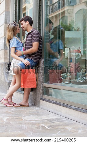 Young attractive romantic couple embracing while shopping in a destination city while on holiday break, outdoors. Travel and lifestyle young people. - stock photo