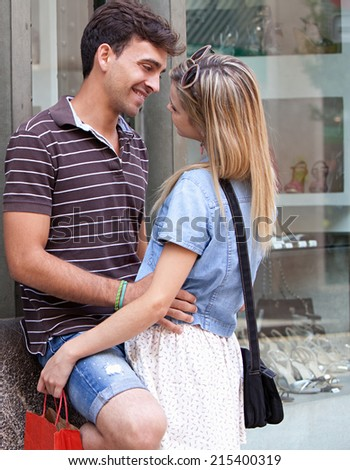 Young attractive romantic couple embracing while shopping in a destination city while on holiday break, outdoors. Travel and consumer lifestyle young people. - stock photo