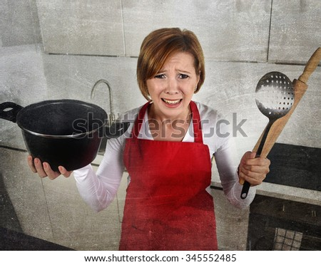 young attractive rookie home cook woman in red apron at home kitchen holding cooking pan and rolling pin crying sad in stress confused and helpless in lifestyle and cooking mess - stock photo