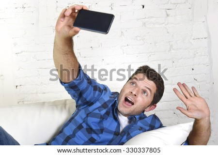 young attractive 30s man taking selfie picture or self video with mobile phone at home sitting on couch smiling happy in use of technology and image concept - stock photo