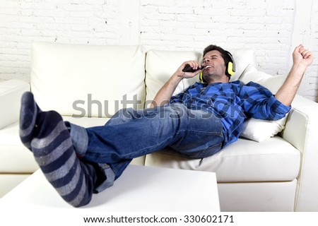 young attractive 20s or 30s man falling asleep on home couch while listening to music with mobile phone and headphones in domestic relax concept - stock photo