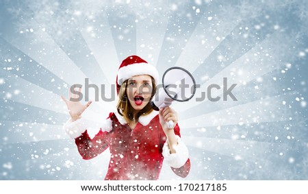 Young attractive Santa girl screaming in megaphone