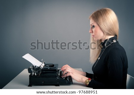 Young attractive secretary writing with an old typewriter. Conceptual image. - stock photo