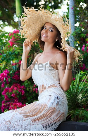 Young attractive sexy woman in hat is posing in tropical garden