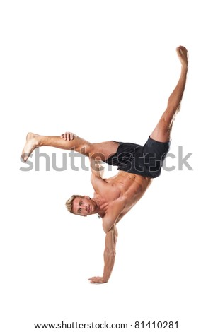 young attractive shirtless male exercising some acrobatic stunts.Studio shot.