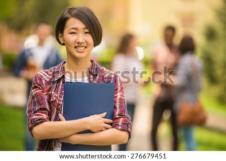 Young attractive smiling asian student outdoors on campus at the university. - stock photo