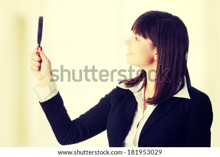 Young attractive smiling business woman looking into a magnifying glass - stock photo