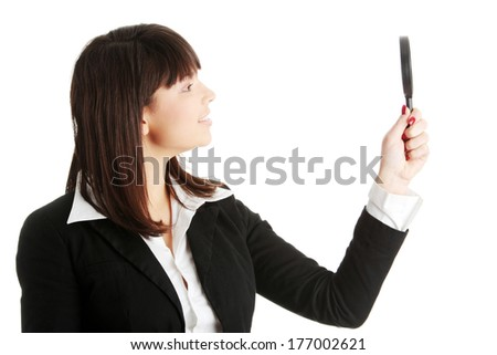 Young attractive smiling business woman looking into a magnifying glass, isolated - stock photo
