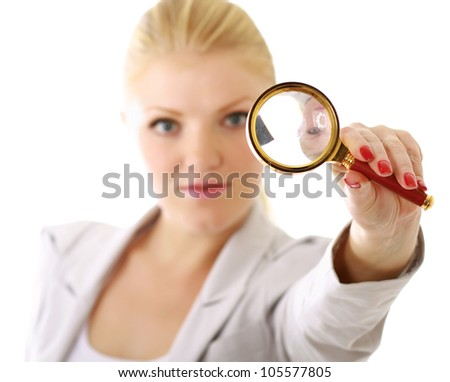 Young attractive smiling businesswoman looking into a magnifying glass, isolated on white background