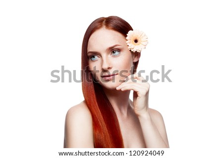 young attractive smiling caucasian female with beige flower in her long natural red hair which gently smiling and soft looking out the camera and softly touching her cheek with her left hand - stock photo