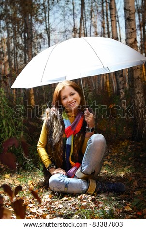 Young attractive smiling girl under umbrella in autumn forest - stock photo