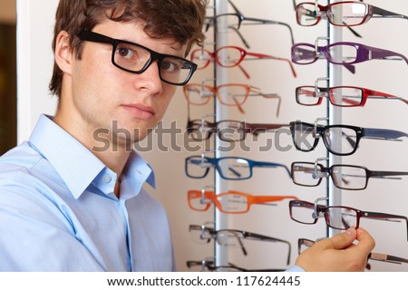 Young attractive smiling man at optician with glasses, background in optician shop - stock photo