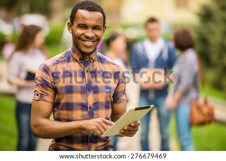 Young attractive smiling mixed race student using tablet outdoors on campus at the university. - stock photo