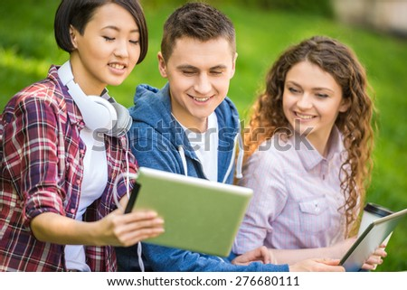 Young attractive smiling students dressed casual  studying outdoors on campus at the university. - stock photo