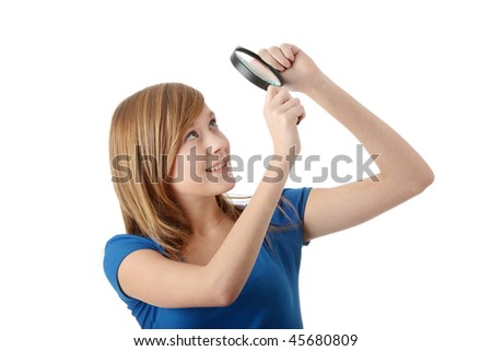 Young attractive smiling teen woman looking into a magnifying glass, isolated - stock photo