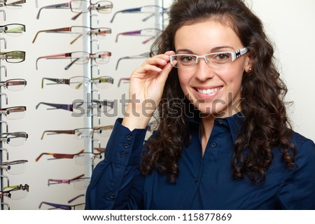 Young attractive smiling woman at optician with glasses, background in optician shop - stock photo