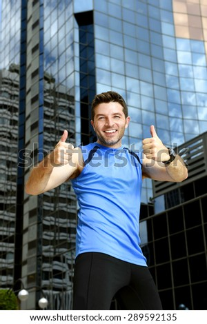 young attractive sport man doing victory and winner thumbs up after running training in urban business district area in fitness, body care and healthy lifestyle concept - stock photo