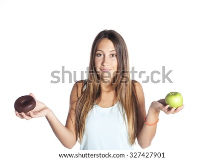 young attractive sport woman holding apple and chocolate donut in her hands in healthy fruit versus sweet junk food temptation in fitness, body health care and healthy nutrition concept - stock photo