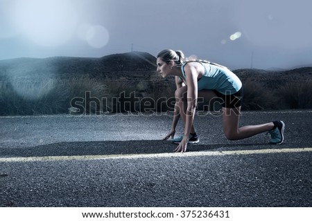 young attractive sport woman posing on start grid style ready for running workout on asphalt road in dramatic harsh light advertising style with lens flare in high performance and energy concept - stock photo
