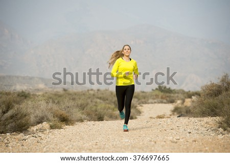young attractive sport woman running on earth trail dirty road with desert mountain landscape background looking happy and healthy in jogging training workout , fitness and wellness concept