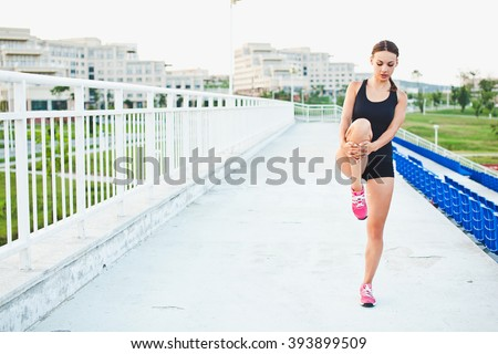 Young attractive sporty girl runner holds her leg while stretching outdoors at stadium of her university campus. Warming up before training. Looking down. Copy space - stock photo