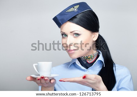 Young attractive stewardess flight attendant holding a cup of coffee espresso in-flight service - stock photo