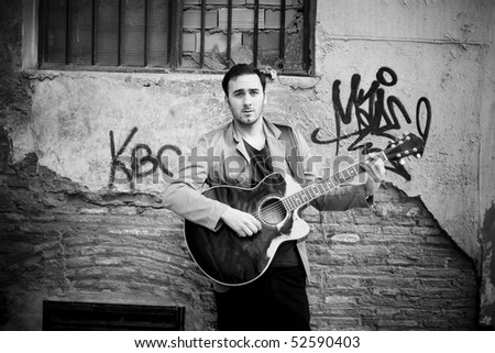 Young attractive street artist playing guitar. - stock photo