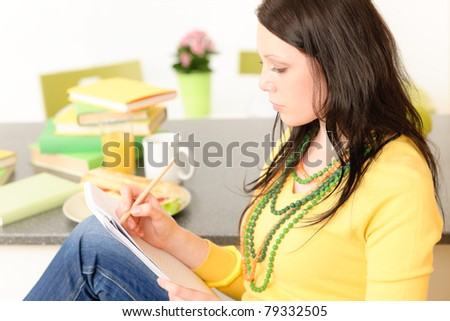 Young attractive student girl thinking and studying in kitchen - stock photo