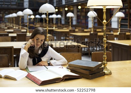 Young attractive student sitting at desk in old university library studying books. - stock photo