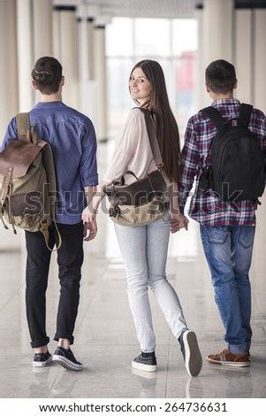 Young attractive students going down the hall  in college - stock photo