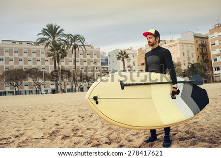 Young attractive surfer sports man wearing a neoprene diving suit and looking at the horizon while carrying his surfing board during a cloudy day - stock photo