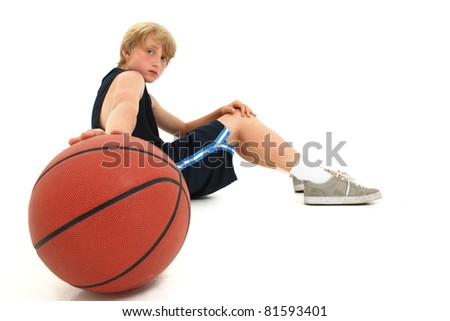 Young attractive teen boy child sitting with basketball in uniform over white serious expression.