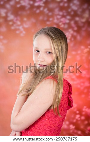 Young attractive teen female in red dress pose in studio - stock photo