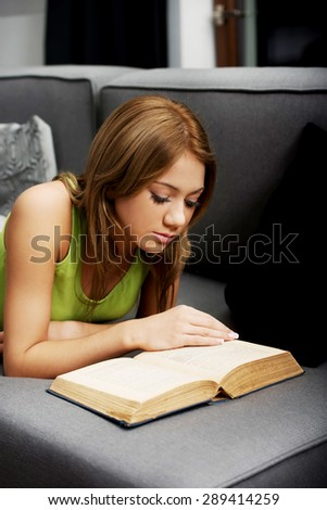 Young attractive teenage woman reading a book on sofa. - stock photo