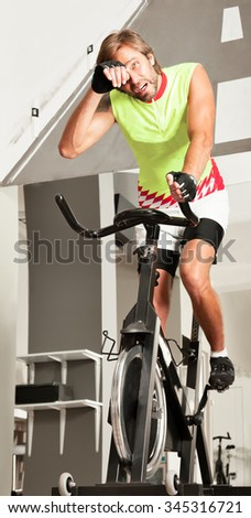 Young attractive tired male is working out in a spinning bike gym.