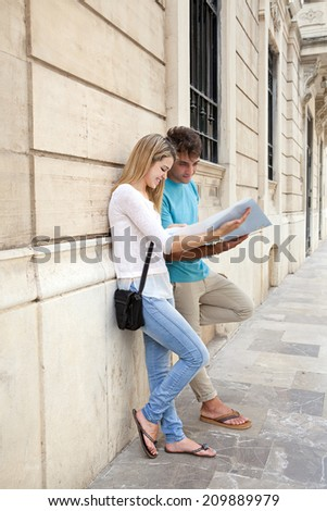 Young attractive tourist couple relaxing in a destination city street with stone buildings, reading a map while on holiday together, outdoors. Travel lifestyle. - stock photo