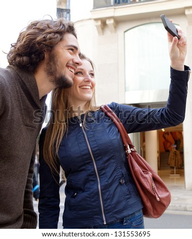 Young attractive tourist couple taking pictures of themselves while visiting a classic architecture city with shops on vacation.