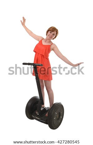 young attractive tourist woman in chic summer dress smiling happy hands free riding electrical segway having fun driving isolated on white background in ecological transport concept - stock photo