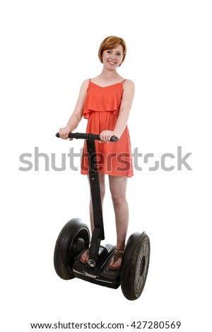 young attractive tourist woman in chic summer dress smiling happy riding electrical segway having fun driving isolated on white background in ecological transport concept - stock photo