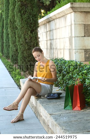 Young attractive tourist woman sitting and relaxing on a stone bench in a green park with sightseeing activities, reading a travel guide book with shopping bags. Travel and lifestyle outdoors. - stock photo