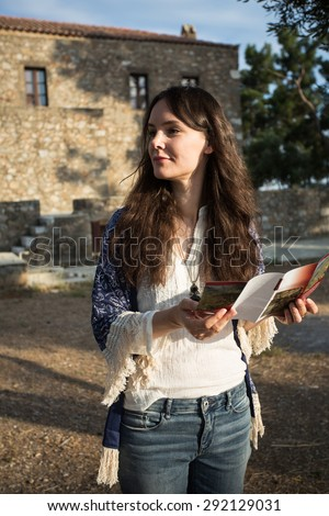 Young attractive tourist woman standing in a green park with sightseeing activities, reading a travel guide book. Travel and lifestyle outdoors. - stock photo
