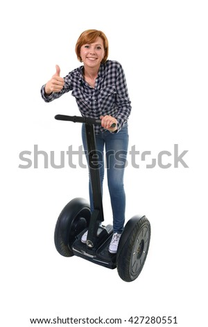 young attractive tourist woman with red hair giving thumb up smiling happy riding electrical segway having fun driving isolated on white background in ecological transport concept - stock photo