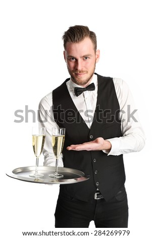 Young attractive waiter wearing a white shirt and black vest, serving 2 glasses of champagne. White background. - stock photo