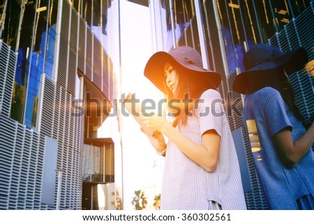 Young attractive well-dressed Asian business woman use digital tablet near skyscrapers. Flare light - stock photo