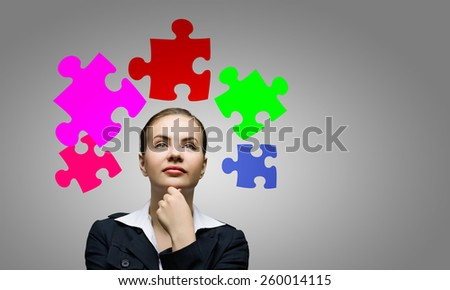 Young attractive woman and colorful puzzles above her head - stock photo